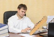 El hombre en la oficina piensa las cuentas Imagen de archivo libre de regalías