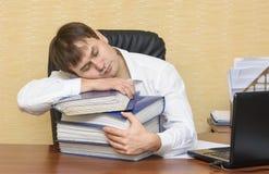 El hombre en la oficina que duerme en una carpeta del documento Fotos de archivo