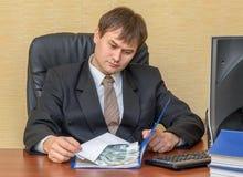 El hombre en la oficina que mira el dinero en un sobre, que miente en una carpeta Foto de archivo