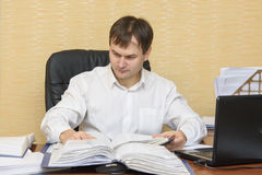 El hombre en la oficina que mira documentos en carpetas Imagenes de archivo
