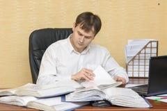 El hombre en la oficina que mira documentos en carpetas Imagen de archivo libre de regalías