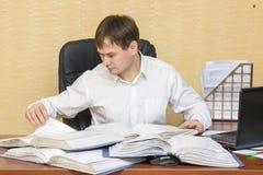 El hombre en la oficina que mira documentos en carpetas Foto de archivo libre de regalías
