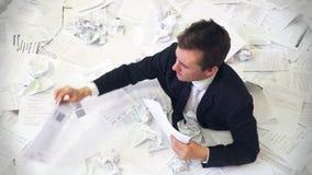 El hombre en la oficina que se ahoga en papel almacen de video