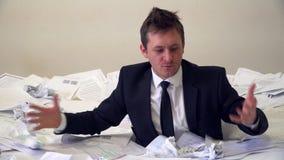 El hombre en la oficina que se ahoga en papel almacen de metraje de vídeo