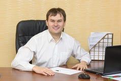El hombre en la oficina que sonríe feliz Fotos de archivo libres de regalías
