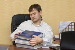 El hombre en la oficina tira para llevar documentos en carpetas Fotografía de archivo libre de regalías