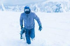 El hombre en la snowboard de la nieve de la montaña Hombre que lleva a cabo a un tablero fotos de archivo
