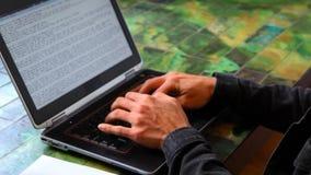 El hombre en la tabla está trabajando con el ordenador portátil metrajes