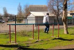 El hombre en las barras desiguales, en el parque en el aire abierto imagenes de archivo