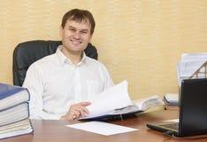 El hombre en los documentos sonrientes de las exploraciones de la oficina Fotografía de archivo libre de regalías