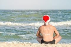 El hombre en los sombreros de Papá Noel con el Año Nuevo de la inscripción en la parte posterior es s Imagen de archivo