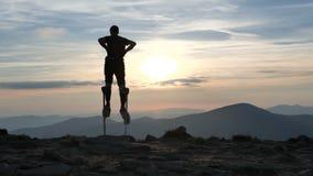 El hombre en los zancos camina en el top de la montaña en la puesta del sol almacen de video