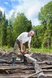 El hombre en madera asierra un árbol una motosierra Imagen de archivo libre de regalías
