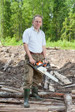 El hombre en madera asierra un árbol una motosierra Fotografía de archivo libre de regalías