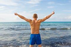 El hombre en nadada azul pone en cortocircuito en la playa fotos de archivo libres de regalías