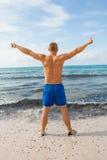 El hombre en nadada azul pone en cortocircuito en la playa imagen de archivo libre de regalías