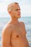 El hombre en nadada azul pone en cortocircuito en la playa Foto de archivo