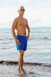 El hombre en nadada azul pone en cortocircuito en la playa imagen de archivo