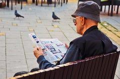 El hombre en negro lee el periódico Fotografía de archivo libre de regalías