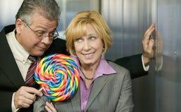 El hombre en oficina ofrece a compañero de trabajo un lollipop Imagen de archivo libre de regalías