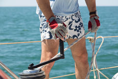 El hombre en pantalones cortos enrolla un torno en un yate Imágenes de archivo libres de regalías