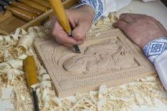 El hombre en ropa ucraniana tradicional talla el icono de madera ortodoxo de la madre de dios y del niño Fotografía de archivo libre de regalías