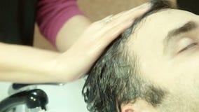 El hombre en salón de belleza lava la cabeza almacen de metraje de vídeo