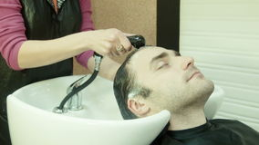 El hombre en salón de belleza lava la cabeza metrajes