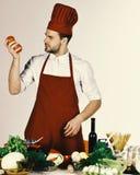 El hombre en sombrero del cocinero y el delantal sostienen los ingredientes Concepto de la preparación de comida El cocinero mira Foto de archivo libre de regalías
