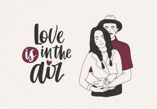 El hombre en el sombrero que se coloca detrás de mujer con las trenzas y abarcamiento sus y amor está en las letras de aire en fo Foto de archivo