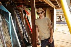 El hombre en sombrero y las gafas de sol que se colocan en la resaca shack Fotos de archivo