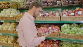 El hombre en supermercado usando una tableta metrajes