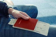 El hombre en tejanos se sienta y se sostiene en su pasaporte de la mano del color rojo con los boletos al avión El ¡de Ð pierde p Fotos de archivo