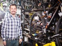 El hombre en tienda de la bicicleta elige para sí mismo la bici de los deportes Fotos de archivo