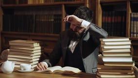 El hombre en traje clásico, profesor con la cara ocupada concentrada se sienta en biblioteca cerca de pilas de libros, estantes e almacen de video