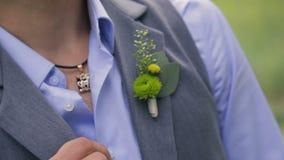 El hombre en traje corrige poco ramo del novio en velo el día de boda metrajes