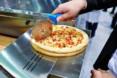 El hombre en traje corta la pizza fotos de archivo