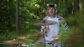 El hombre en traje de la cebra juega en los tambores, sonrisas, goza, va loco en bosque entre los árboles El batería está jugando almacen de metraje de vídeo