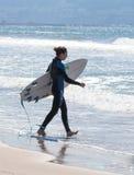 El hombre en traje de la prenda impermeable del color camina en la playa con el tablero Foto de archivo