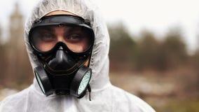 El hombre en traje del bio-peligro y careta antigás mira derecho en la cámara almacen de video