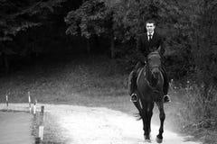 El hombre en traje negro monta un caballo Foto de archivo