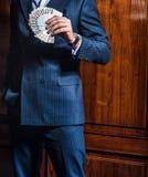 El hombre en traje presenta con las tarjetas en fondo de madera fotografía de archivo libre de regalías