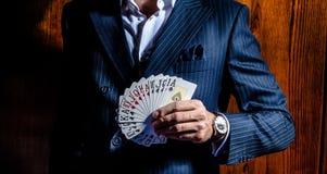 El hombre en traje presenta con las tarjetas en fondo de madera imagenes de archivo