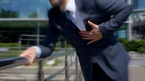 El hombre en traje se siente mal el aire libre, efecto mareado, problemas del corazón, síntoma de la enfermedad foto de archivo