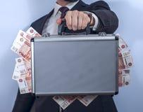El hombre en traje sostiene la cartera del metal llena de dinero Foto de archivo libre de regalías