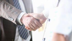 El hombre en traje y el lazo dan la mano como hola en oficina imagen de archivo