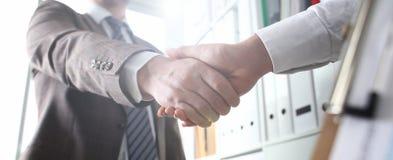 El hombre en traje y el lazo dan la mano como hola en oficina fotos de archivo