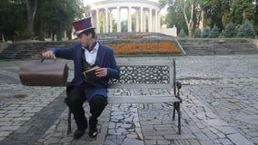 El hombre en traje y sombrero de copa retros saca el libro de su bolso almacen de video