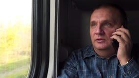 El hombre en el tren está hablando en el teléfono