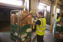 El hombre en un almacén sostiene y explora una caja para la entrega imágenes de archivo libres de regalías